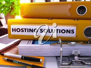 Yellow Ring Binder with Inscription Hosting Solutions on Background of Working Table with Office Supplies and Laptop. Hosting Solutions Business Concept on Blurred Background. 3D Render.