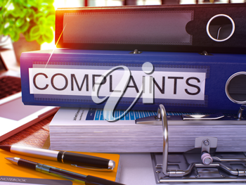 Blue Ring Binder with Inscription Complaints on Background of Working Table with Office Supplies and Laptop. Complaints Business Concept on Blurred Background. 3D Render.