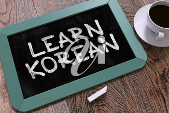 Learn Korean - Blue Chalkboard with Hand Drawn Text and White Cup of Coffee on Wooden Table. Top View. 3D Render.