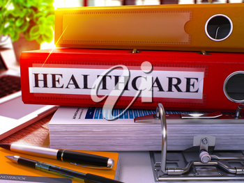 Red Ring Binder with Inscription Healthcare on Background of Working Table with Office Supplies and Laptop. Healthcare Business Concept on Blurred Background. 3D Render.