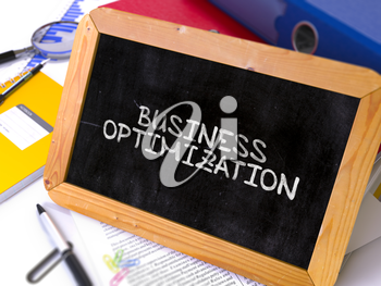 Business Optimization Handwritten on Chalkboard. Composition with Small Chalkboard on Background of Working Table with Ring Binders, Office Supplies, Reports. Blurred, Toned Image. 3D Render.