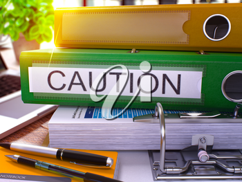 Green Office Folder with Inscription Caution on Office Desktop with Office Supplies and Modern Laptop. Caution Business Concept on Blurred Background. Caution - Toned Image. 3D Render.
