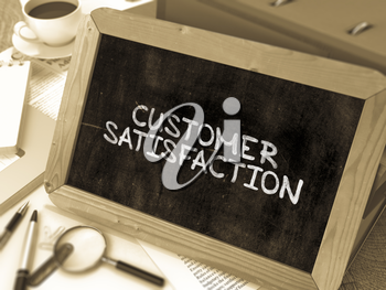 Handwritten Customer Satisfaction on a Chalkboard. Composition with Chalkboard and Ring Binders, Office Supplies, Reports on Blurred Background. Toned Image. 3D Render.