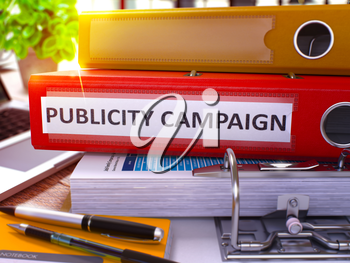 Publicity Campaign - Red Office Folder on Background of Working Table with Stationery and Laptop. Publicity Campaign Business Concept on Blurred Background. Publicity Campaign Toned Image. 3D.