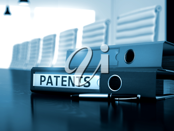 Patents - Business Illustration. Patents. Business Concept on Toned Background. Patents - Business Concept on Toned Background. Binder with Inscription Patents on Desk. 3D.
