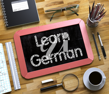 Learn German on Small Chalkboard. Learn German - Red Small Chalkboard with Hand Drawn Text and Stationery on Office Desk. Top View. 3d Rendering.