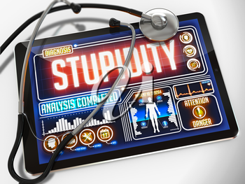 Medical Tablet with the Diagnosis of Stupidity on the Display and a Black Stethoscope on White Background.