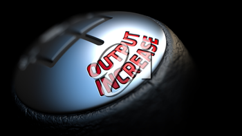 Output Increase - Red Text on Car's Shift Knob on Black Background. Close Up View. Selective Focus.