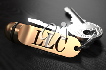 Keys and Golden Keyring with the Word LLC - Limited Legal Liability - over Black Wooden Table with Blur Effect.