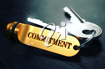Keys with Word Commitment on Golden Label over Black Wooden Background. Closeup View, Selective Focus, 3D Render. Toned Image.