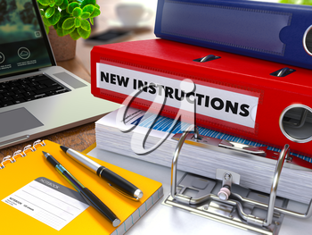 Red Ring Binder with Inscription New Instructions on Background of Working Table with Office Supplies, Laptop, Reports. Toned Illustration. Business Concept on Blurred Background.
