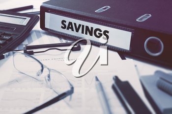 Savings - Office Folder on Background of Working Table with Stationery, Glasses, Reports. Business Concept on Blurred Background. Toned Image.