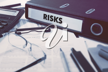 Risks - Ring Binder on Office Desktop with Office Supplies. Business Concept on Blurred Background. Toned Illustration.