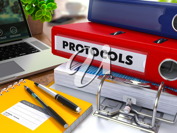 Red Ring Binder with Inscription Protocols on Background of Working Table with Office Supplies, Laptop, Reports. Toned Illustration. Business Concept on Blurred Background.