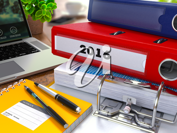 Red Ring Binder with Inscription 2016 on Background of Working Table with Office Supplies, Laptop, Reports. Toned Illustration. Business Concept on Blurred Background.