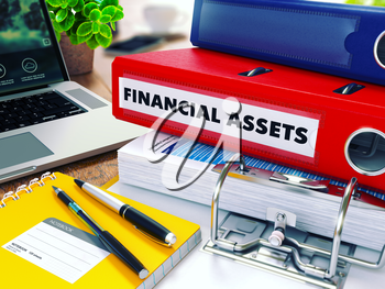 Financial Assets - Red Ring Binder on Office Desktop with Office Supplies and Modern Laptop. Business Concept on Blurred Background. Toned Illustration.