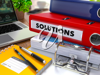Red Ring Binder with Inscription Solutions on Background of Working Table with Office Supplies, Laptop, Reports. Toned Illustration. Business Concept on Blurred Background.