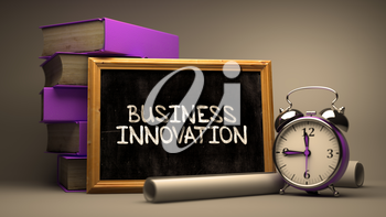 Business Innovation Handwritten on Chalkboard. Time Concept. Composition with Chalkboard and Stack of Books, Alarm Clock and Scrolls on Blurred Background. Toned Image.