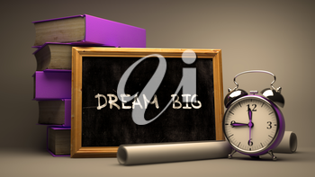 Dream Big - Chalkboard with Hand Drawn Text, Stack of Books, Alarm Clock and Rolls of Paper on Blurred Background. Toned Image.