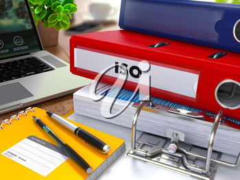 Red Ring Binder with Inscription ISO on Background of Working Table with Office Supplies, Laptop, Reports. Toned Illustration. Business Concept on Blurred Background.