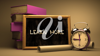 Learn More - Chalkboard with Hand Drawn Text, Stack of Books, Alarm Clock and Rolls of Paper on Blurred Background. Toned Image.