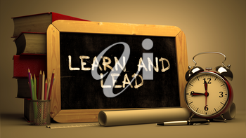 Learn and Lead Concept Hand Drawn on Chalkboard. Blurred Background. Toned Image.
