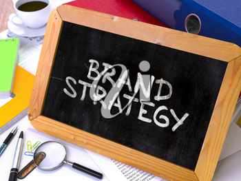 Brand Strategy - Chalkboard with Hand Drawn Text, Stack of Office Folders, Stationery, Reports on Blurred Background. Toned Image.
