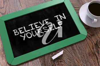 Believe in Yourself - Motivational Quote. Green Chalkboard with Hand Drawn Text and White Cup of Coffee on Wooden Table. Top View.