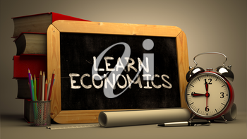 Learn Economics. Motivational Quote Handwritten by white Chalk on a Blackboard. Composition with Small Chalkboard and Stack of Books, Alarm Clock and Rolls of Paper on Blurred Background. Toned Image.