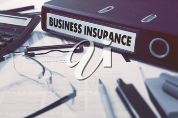 Ring Binder with inscription Business Insurance on Background of Working Table with Office Supplies, Glasses, Reports. Toned Illustration. Business Concept on Blurred Background.