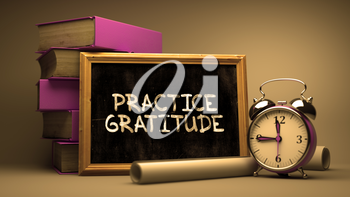 Practice Gratitude Handwritten by white Chalk on a Blackboard. Composition with Small Chalkboard and Stack of Books, Alarm Clock and Rolls of Paper on Blurred Background. Toned Image.