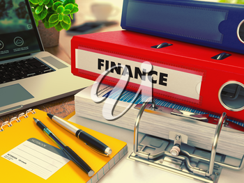 Red Office Folder with Inscription Finance on Office Desktop with Office Supplies and Modern Laptop. Business Concept on Blurred Background. Toned Image.