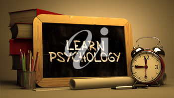 Handwritten Learn Psychology on a Chalkboard. Composition with Chalkboard and Stack of Books, Alarm Clock and Rolls of Paper on Blurred Background. Toned Image.