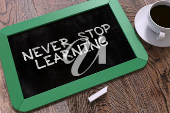 Never Stop Learning - Motivation Quote Handwritten on Green Chalkboard. Business Concept. Composition with Chalkboard and Cup of Coffee. Top View Image.