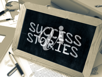 Handwritten Success Stories on a Chalkboard. Composition with Chalkboard and Ring Binders, Office Supplies, Reports on Blurred Background. Toned Image.