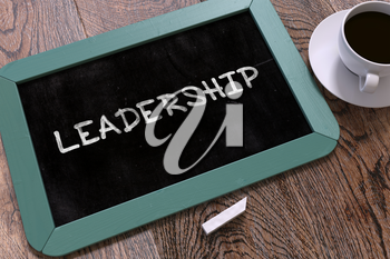 Leadership - Blue Chalkboard with Hand Drawn Text and White Cup of Coffee on Wooden Table. Top View.