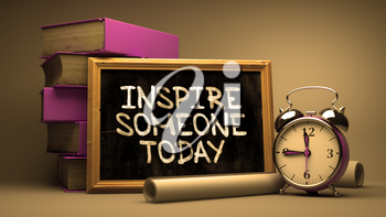 Handwritten Inspire Someone Today on a Chalkboard. Composition with Chalkboard and Stack of Books, Alarm Clock and Rolls of Paper on Blurred Background. Toned Image.