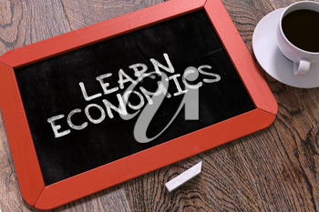 Learn Economics Handwritten on Red Chalkboard. Business Concept. Composition with Chalkboard and Cup of Coffee. Top View Image.
