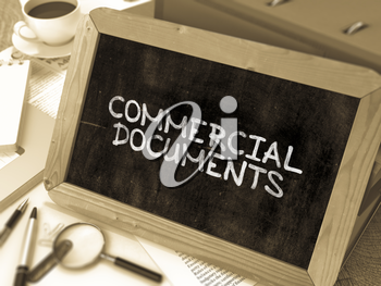 Commercial Documents Handwritten by White Chalk on a Blackboard. Composition with Small Chalkboard on Background of Working Table with Office Folders, Stationery, Reports. Blurred Background. Toned Im