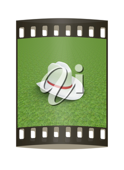 White hat with a red ribbon on a green grass background. 3d. The film strip