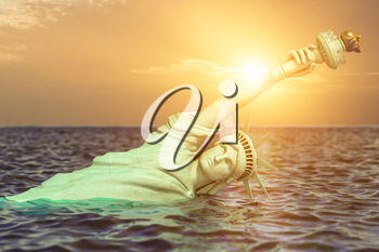 Destroyed Statue of liberty in the sunset half covered by rising ocean level.  Apocalypse of USA, America and the end of civilization concept. 3d illustration
