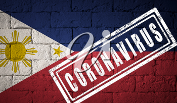Flag of the Philippines with original proportions. stamped of Coronavirus. brick wall texture. Corona virus concept. On the verge of a COVID-19 or 2019-nCoV Pandemic.