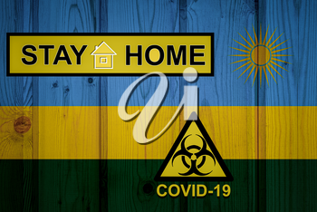 Flag of the Rwanda in original proportions. Quarantine and isolation - Stay at home. flag with biohazard symbol and inscription COVID-19.
