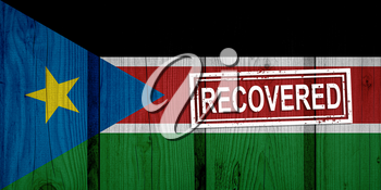 flag of South Sudan that survived or recovered from the infections of corona virus epidemic or coronavirus. Grunge flag with stamp Recovered
