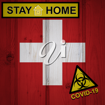 Flag of the Switzerland in original proportions. Quarantine and isolation - Stay at home. flag with biohazard symbol and inscription COVID-19.