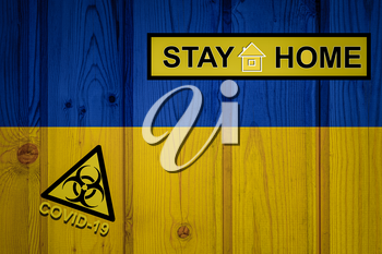 Flag of the Ukraine in original proportions. Quarantine and isolation - Stay at home. flag with biohazard symbol and inscription COVID-19.